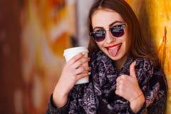Nätt flicka som framme står av väggen med koppen kaffe Arkivbilder