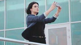 Nätt flicka som gör selfies på smartphonen En ung brunettkvinna med en mobiltelefon Grejer och folk Smartphone in lager videofilmer