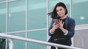 Nätt flicka som gör selfies på smartphonen En ung brunettkvinna med en mobiltelefon Grejer och folk Smartphone in stock video