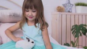 Nätt flicka som har gyckel, kramar och spelar med dekorativ kanin lager videofilmer