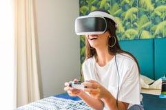 Nätt flicka som har gyckel som spelar videogames med virtuell verklighetapparaten royaltyfria bilder