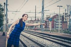 Nätt flicka som liftar längs spåren fotografering för bildbyråer