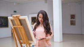 Nätt flicka som rymmer en borste som målar en bild stock video