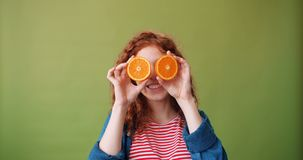 Nätt flicka som rymmer nya apelsiner nära hennes ögon som ler på grön bakgrund lager videofilmer