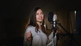 Nätt flicka som sjunger in i studiomikrofonen Flickan bär hörlurar på en vit bakgrund I det låga ljuset av arkivfilmer