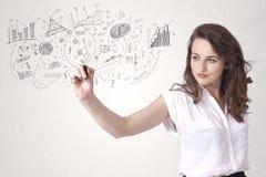 Nätt flicka som skissar grafer och diagram på väggen Arkivfoton