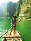 Nätt flicka som svävar på en bambuflotte Arkivfoto