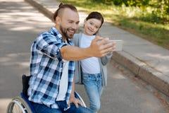 Nätt flicka som tar fotoet på telefonen med hennes farsa Arkivfoto