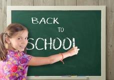 Nätt flicka som tillbaka skriver till skolan på svart tavla Arkivbilder