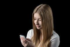 Nätt flicka som tycker om det sociala nätverket på hennes mobiltelefon Royaltyfri Foto