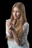 Nätt flicka som tycker om det sociala nätverket på hennes mobiltelefon Royaltyfria Bilder