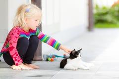 Nätt flicka som utanför klappar en katt Arkivfoto