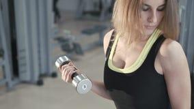 Nätt flicka som utarbetar med hantlar i idrottshallen i 4K lager videofilmer