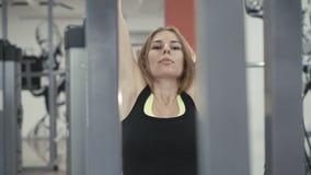 Nätt flicka som utarbetar med simulatorn för muskler på armar i idrottshallen i 4k lager videofilmer
