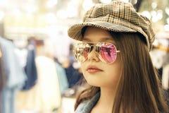 N?tt flickablondin med l?ngt h?r i ett rutigt lock, exponeringsglas, rosa kl?nning fotografering för bildbyråer