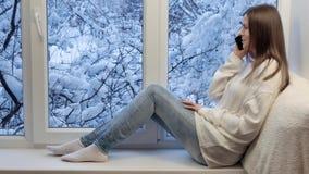 Nätt flickasammanträde på fönsterbrädan som talar på smartphonen utvändig vinter arkivfilmer