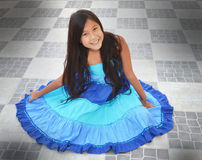 Nätt flickasammanträde som ha på sig den färgglada klänningen   Royaltyfria Bilder