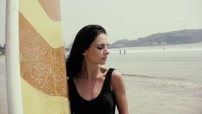 Nätt flickasurfare eller härlig kvinna, sexig slank brunett, i baddräkt med sexibakdelar som rymmer på den gula surfingbrädan lager videofilmer