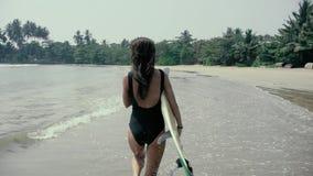 Nätt flickasurfare eller härlig kvinna, sexig slank brunett, i baddräkt med sexibakdelar som rymmer på den gula surfingbrädan stock video