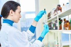Nätt forskare med den volymetriska flaskan arkivbild