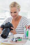 Nätt fotoredaktör som ser hennes digitala kamera Arkivbild