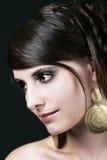 Nätt framsida av en ung kvinna med stora örhängen arkivbild