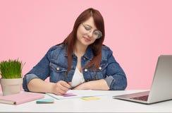 Nätt fyllig flicka som gör studier på tabellen royaltyfri foto