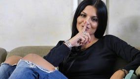 Nätt göra för ung kvinna hyssjar tecknet med fingret på kanter Royaltyfria Bilder
