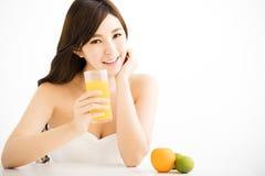 Nätt glad hållande apelsinfruktsaft för ung kvinna Fotografering för Bildbyråer