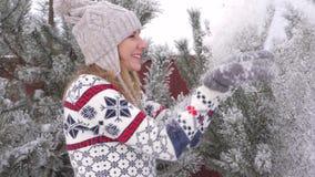 Nätt glad kvinna som har gyckel i vintern som blåser snöultrarapid 180fps lager videofilmer