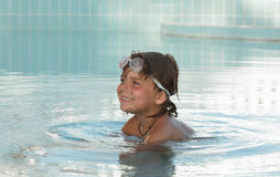 Nätt glat och att le lilla flickan som tycker om hennes simningtid Royaltyfri Foto