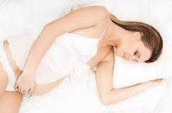 Nätt gravid kvinna i en säng arkivfoton