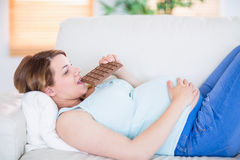 Nätt gravid kvinna som äter den stora stången av choklad Arkivbilder