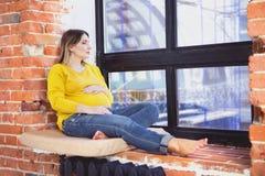 Nätt gravid kvinna som sitter inomhus nära fönster arkivfoto