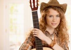Nätt guitarplayerflicka som omfamnar gitarren Royaltyfria Bilder