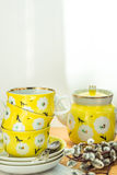 Nätt gul teservis med den staplade koppar, tefat och krukan, blom- prydnad, lantlig kökinre, mjuka solljusfläckar, vår Fotografering för Bildbyråer