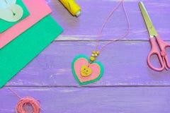 Nätt halsband för filthjärtahänge Sax tråd, filtark, pappers- mall på en purpurfärgad träbakgrund Royaltyfri Fotografi