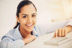 Nätt indisk affärskvinna för Closeup som ler på skrivbordet i modernt av fotografering för bildbyråer