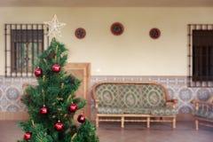 Nätt julgran med några röda bollar och en gullig stjärna Arkivfoto