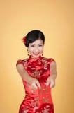 Nätt kinesisk ung kvinna som rymmer det röda facket för lyckligt kinesiskt nytt år Royaltyfri Fotografi