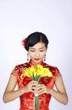 Nätt kinesisk ung kvinna som rymmer en grupp av gula påskliljor Arkivbilder