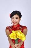 Nätt kinesisk ung kvinna som rymmer en grupp av gula påskliljor Fotografering för Bildbyråer