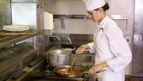 Nätt kock som förbereder grönsaker i en panna lager videofilmer