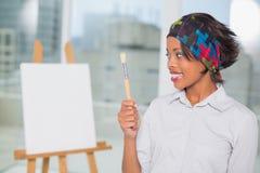 Nätt konstnär som ser hennes borste Arkivbild