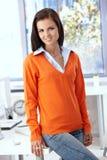 Nätt kontorsarbetare som ler i orange pullover Royaltyfri Fotografi