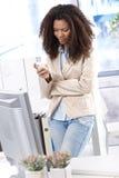 Nätt kontorsarbetare som texting på den mobila telefonen Arkivfoton
