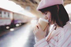 Nätt kopp för kvinnahållkaffe, varmt svart kaffe för drink i morgon under att vänta drevet på drevstationen arkivfoto