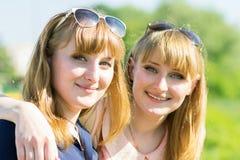 Nätt kopplar samman flickor som har gyckel på utomhus- sommar, parkerar Royaltyfri Bild