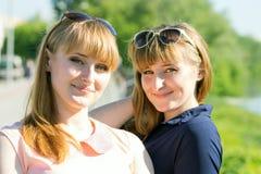 Nätt kopplar samman flickor som har gyckel på utomhus- sommar, parkerar Royaltyfria Foton