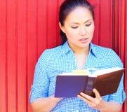 Nätt kvinna för blandat lopp som läser den heliga bibeln royaltyfri fotografi